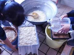 固まってきた豆腐のもとを集めて容器に入れる様子.JPG